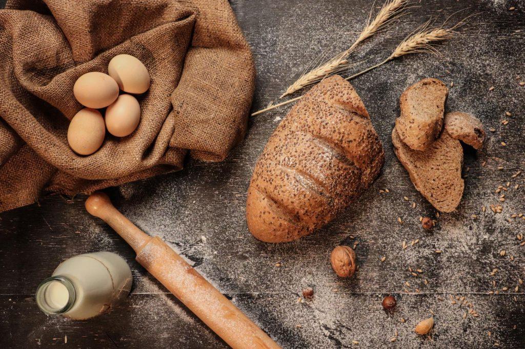 Brot auf dem Tisch mit Eiern und Milch.