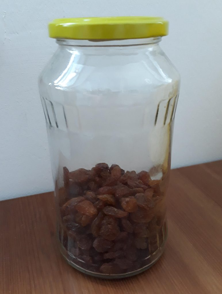 A glass container with raisins in it. To make yeast from scratch, you need a tall container. A recycled glass works just fine, like this once that once held some cherries.
