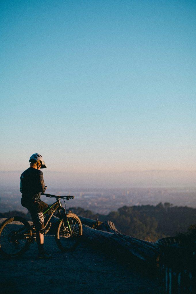 Ein Radfahrer schaut auf die tadt herab. Pendeln mit dem Fahrrad ist nicht nur gut, um sich nicht einem Infektionsrisiko mit dem Coronavirus auszusetzen. Es ist außerdem extrem umweltfreundlich und auch noch gut für die Gesundheit!
